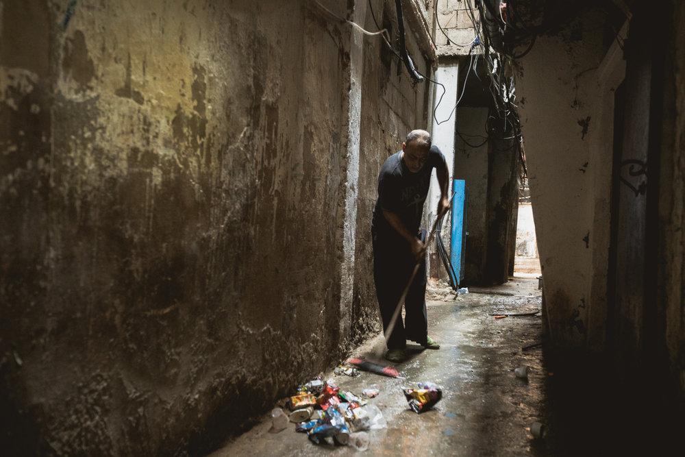 An elderly man sweeps trash away from his door.