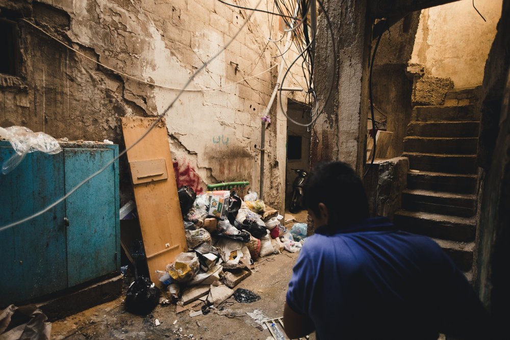A man covers his face as he walks by a pile of rotting trash.