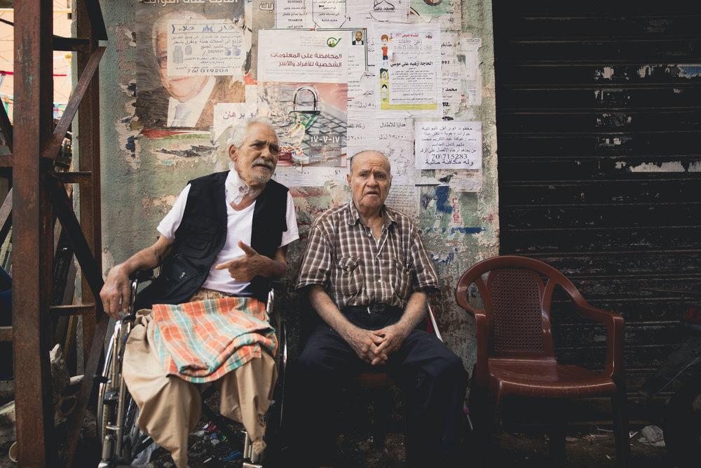 Two elderly Palestinians sit and talk on a street corner inside Shatila.