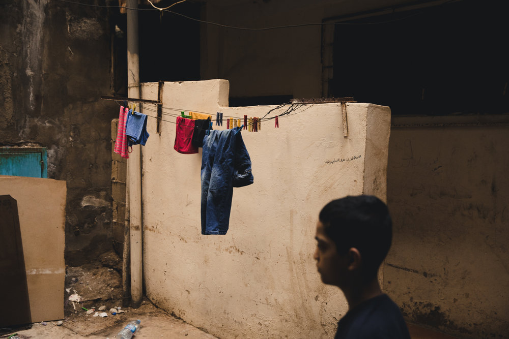 A young man walks past laundry drying inside an alleyway.