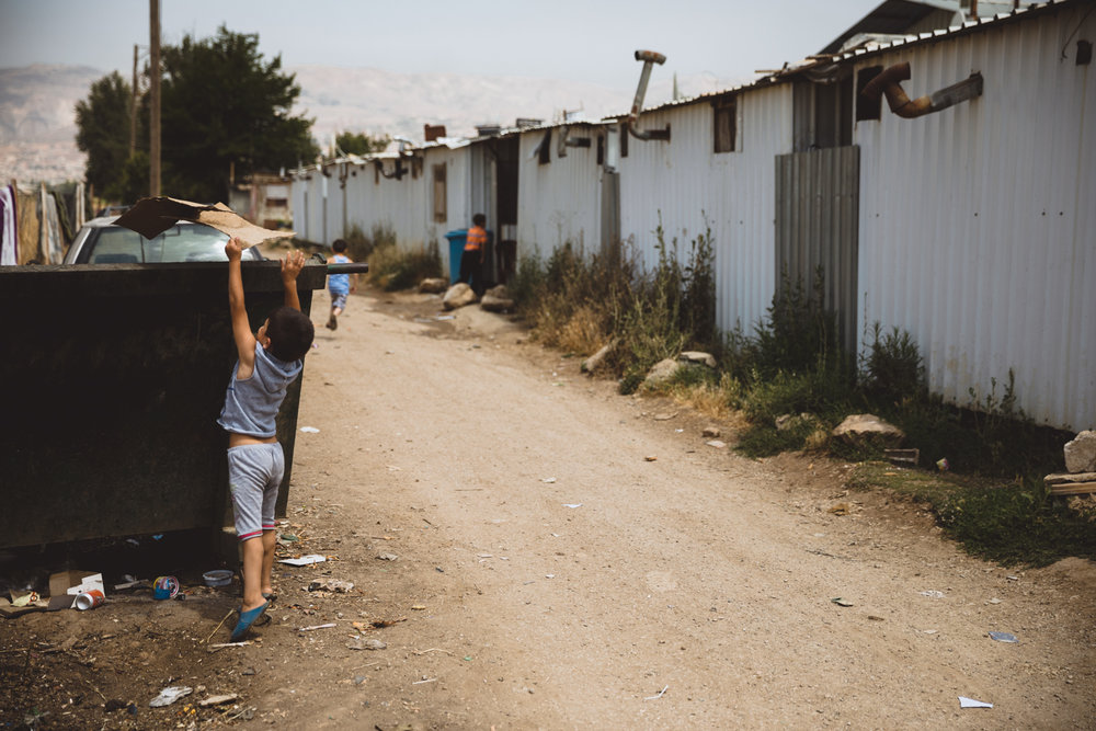 A boy throws out trash outside the steel refugee compound he lives in.