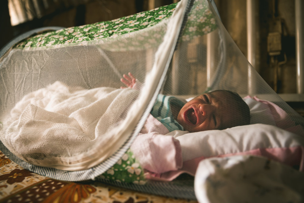 At the time of this photograph the infant was only five days old. A mosquito net protects her from insects.