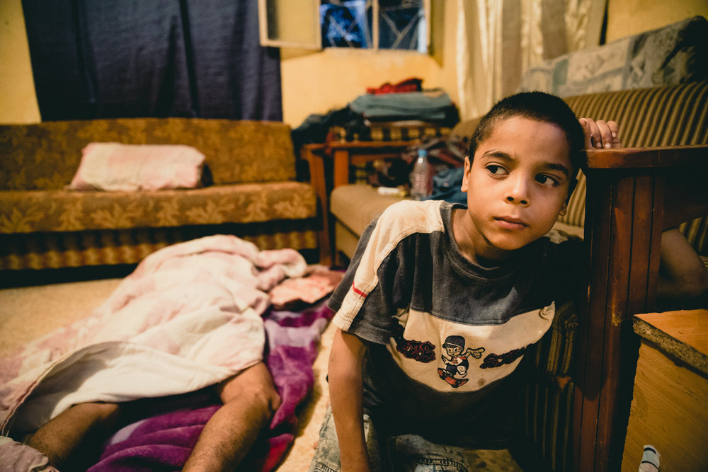 A young boy sits quietly while members of his family sleep in the room they all share.
