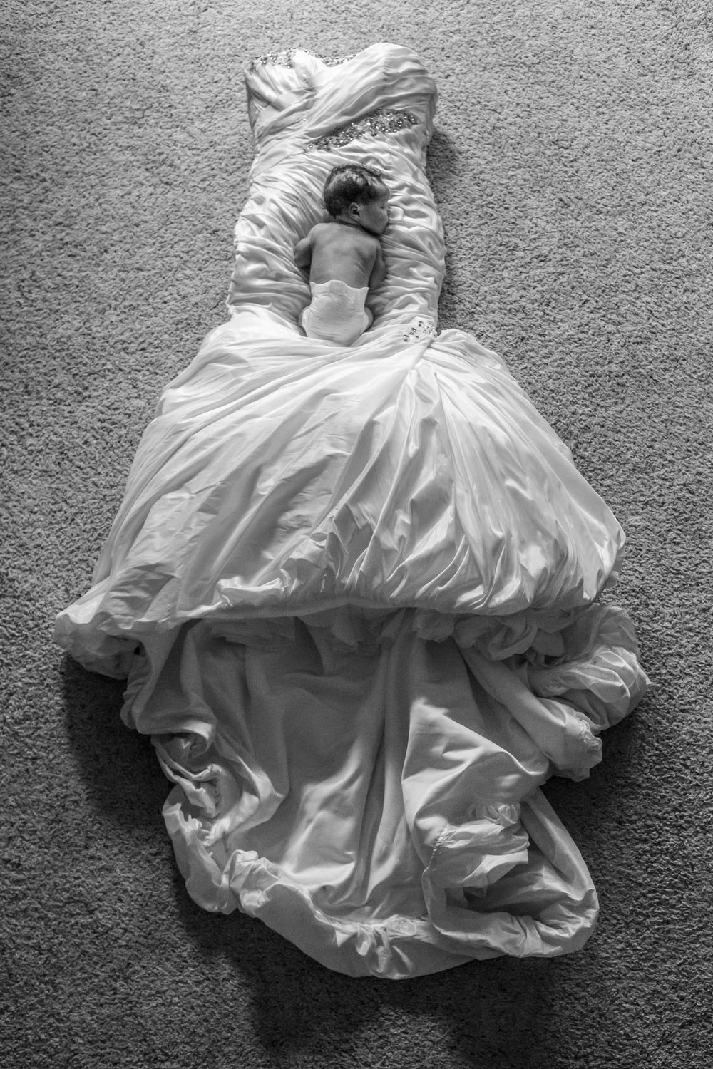 Black and white photo of baby sleeping on wedding dress