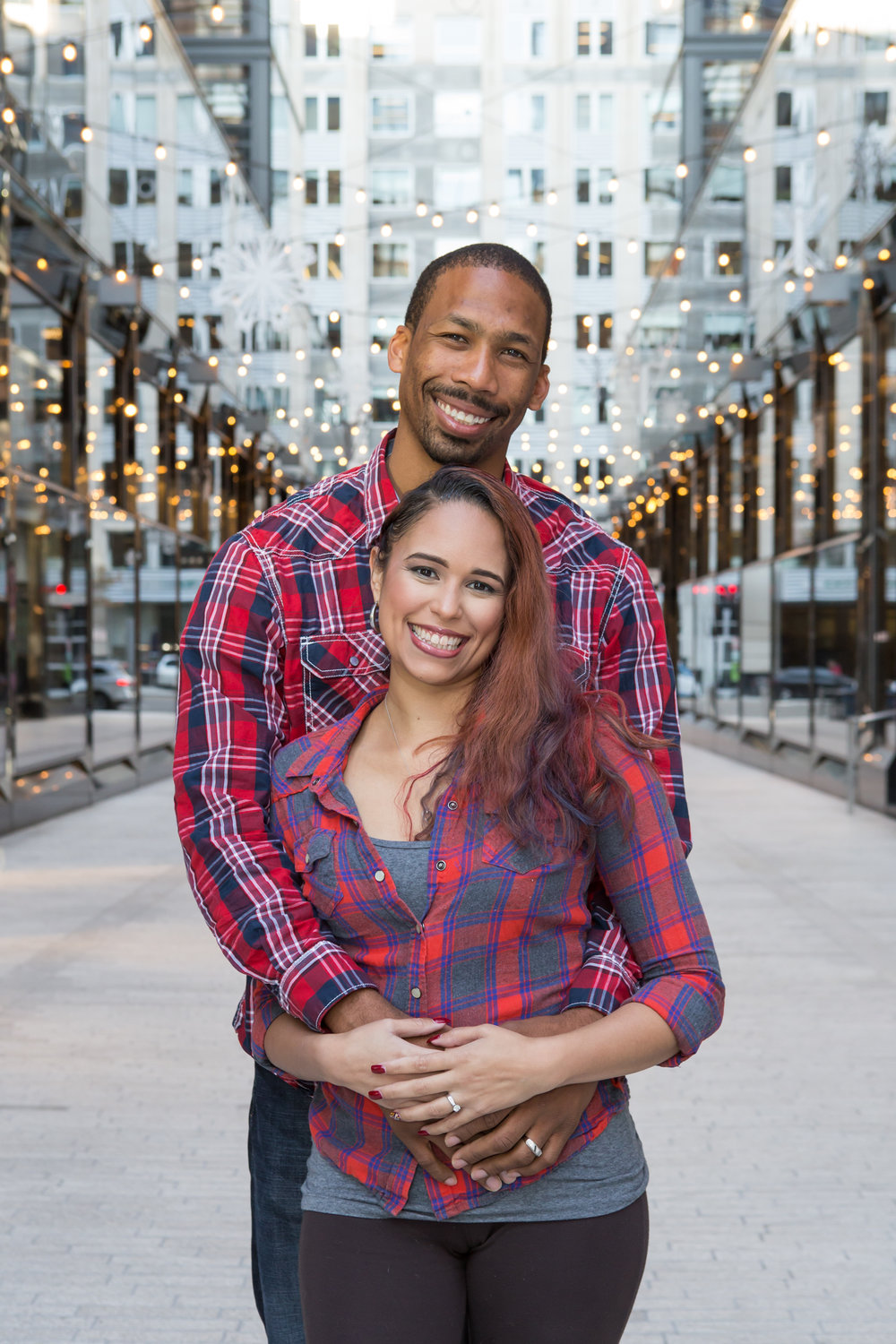 Couple wearing plaid shirts embracing while looking at the camera