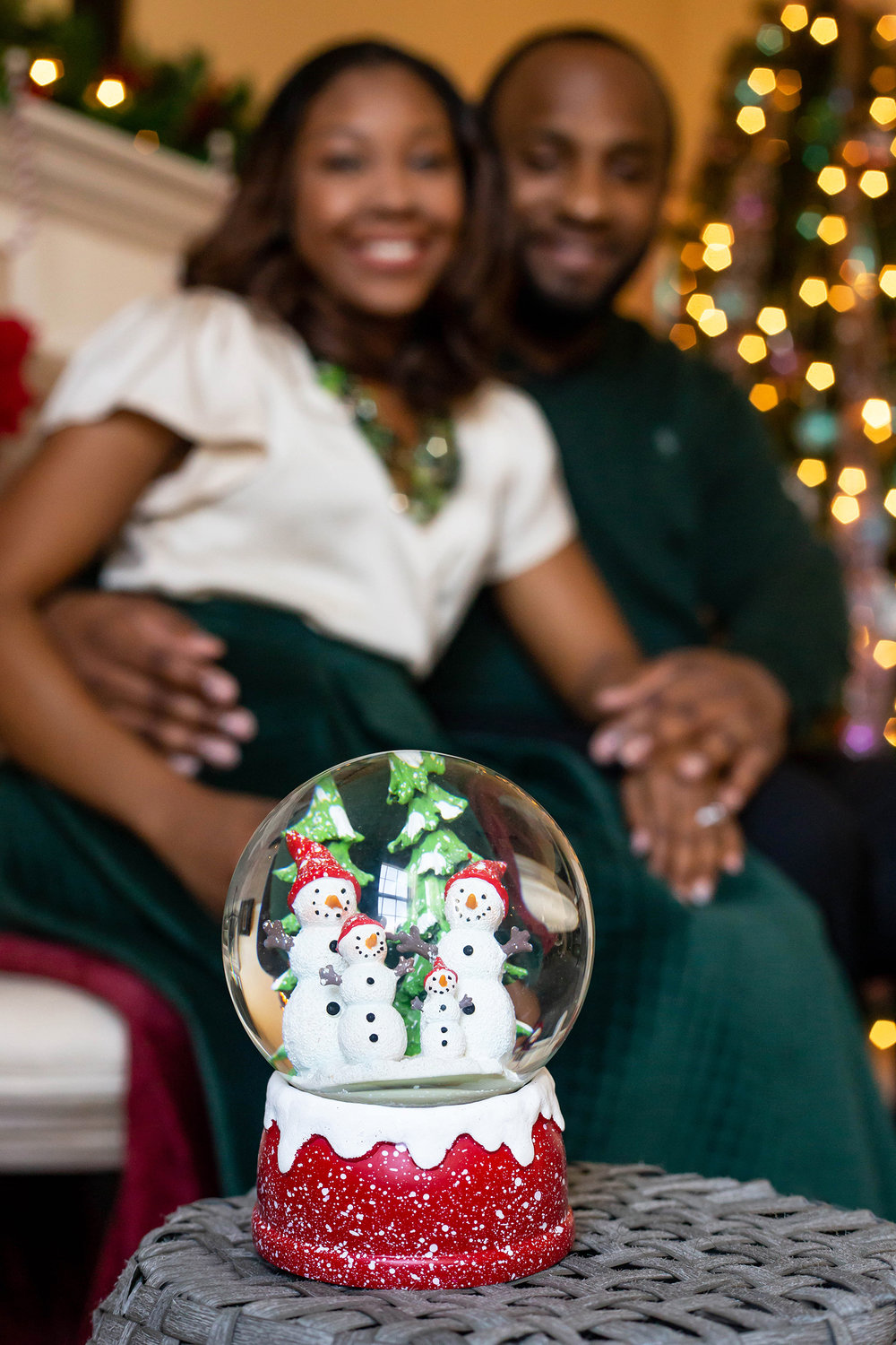 Photo of snowman family snow globe with couple smiling in the background