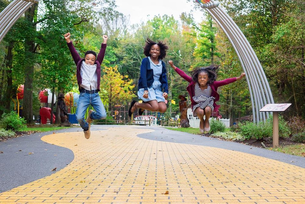 Three kids jumping in the air over a yellow brick road