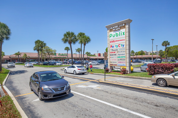 Country Club Plaza Parking Lot Entrance with Monument Sign and Storefronts in Background
