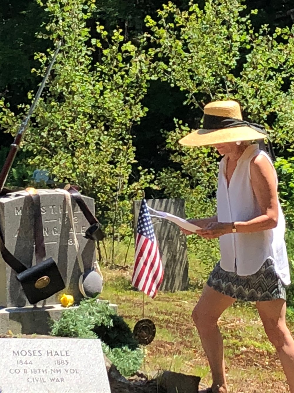 Orange Selectboard Chair Dorothy Behlen Heinrichs lays a flag on the French Cemetery grave of a Civil War Veteran.