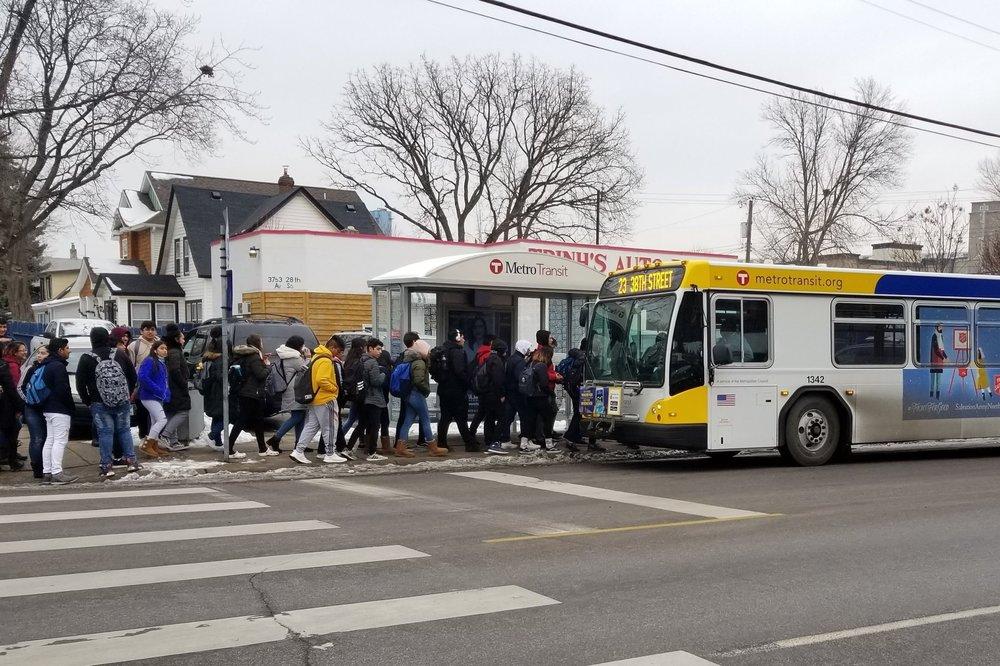 A large number of youth line up to board a Metro Transit bus at a bus stop located at a street corner. Their bookbags suggest they are going to school, and the lack of leaves and heavy coats indicate that it is winter. Many of the youth are people of color.