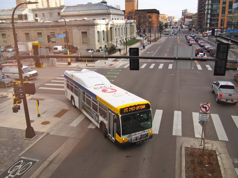 An overhead view of the 17C Metro Transit bus towards 24th St - Uptown, as it makes a right-hand turn across a crosswalk in downtown Minneapolis. There are no pedestrians in the picture, and several cars heading in the opposite direction of the bus as it makes its turn.