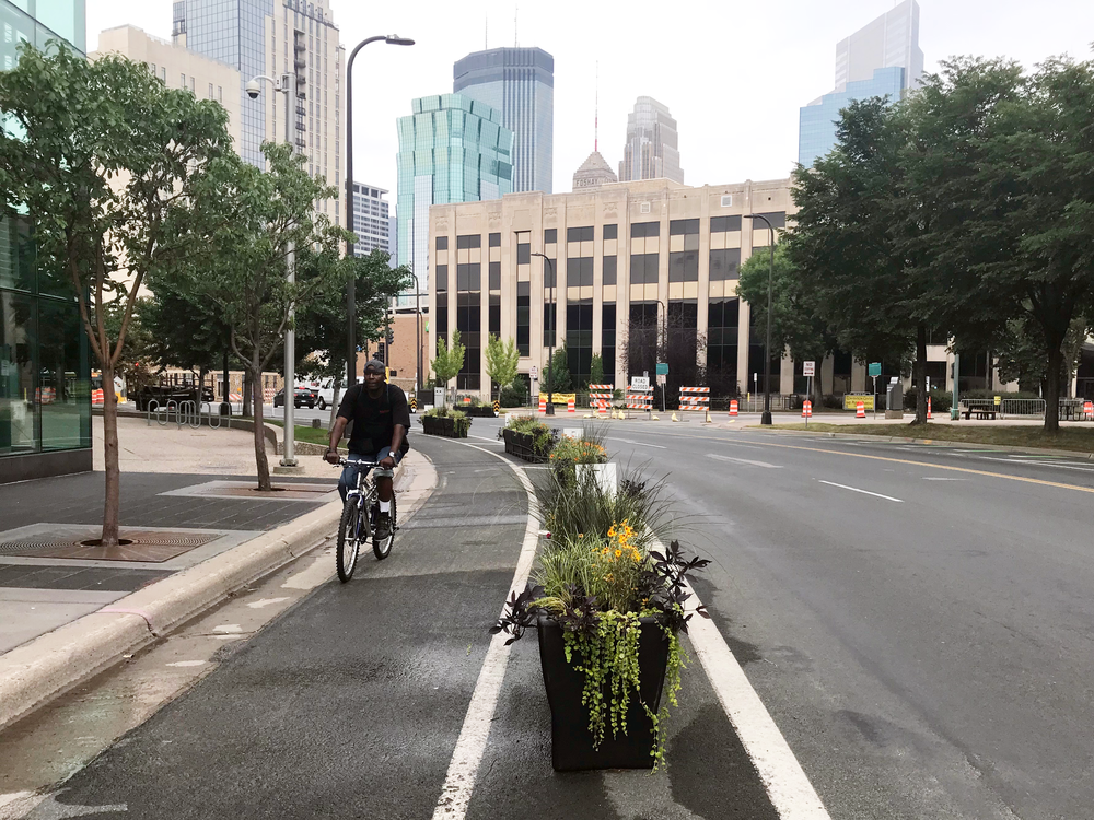 A black man in a tee-shirt and jeans rides on a mountain bike in a protected bike lane on a 4 lane street. The bike lane is separated from motor vehicle traffic by a row of planters with flowers and greenery growing in them. A sidewalk borders the other side, and there are a few cars in the distance, heading the opposite direction