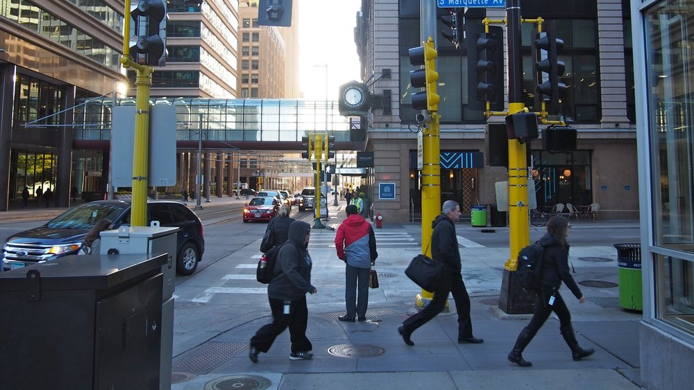 People finish crossing the street and walk on the sidewalk in downtown Minneapolis, amid a forest of yellow traffic signal masts. A small SUV completes a left turn as the walk signal appears for those heading in the direction perpendicular to the folks finishing their crossing. The scene occurs at either the early morning or early evening hours.