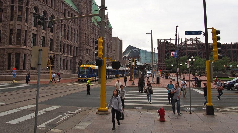 Numerous people cross the street with the right-of-way at a traffic signal in downtown Minneapolis, next to the Green Line, with US Bank Stadium in the background.