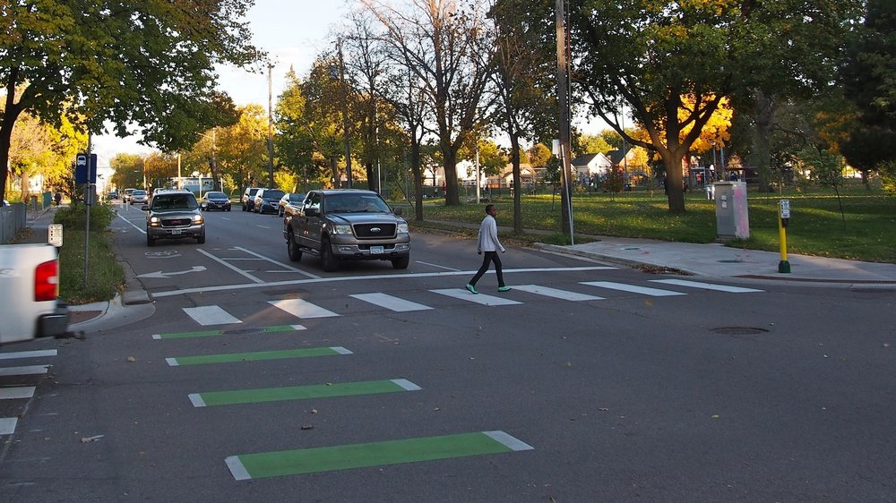 A young black boy crosses the street in a cross walk ahead of a pick-up truck driver waiting at the stop sign. There is green paint in view, indicating the presence of a bike lane, and reflecting the fact that this street has treatments taht keep people on bikes and walking in mind as users.