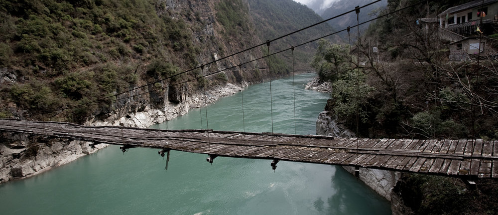 An old bridge between Qiunatong and Wuli, Yunnan. A new bridge sits alongside of the old one. As tourism becomes a more important part of the local economy the government is making improvements to the local road system. Villagers and tourists who would have come here a few years ago would have needed to walk or use a four wheel drive vehicle. Now there is van service as far as Qiunatong.