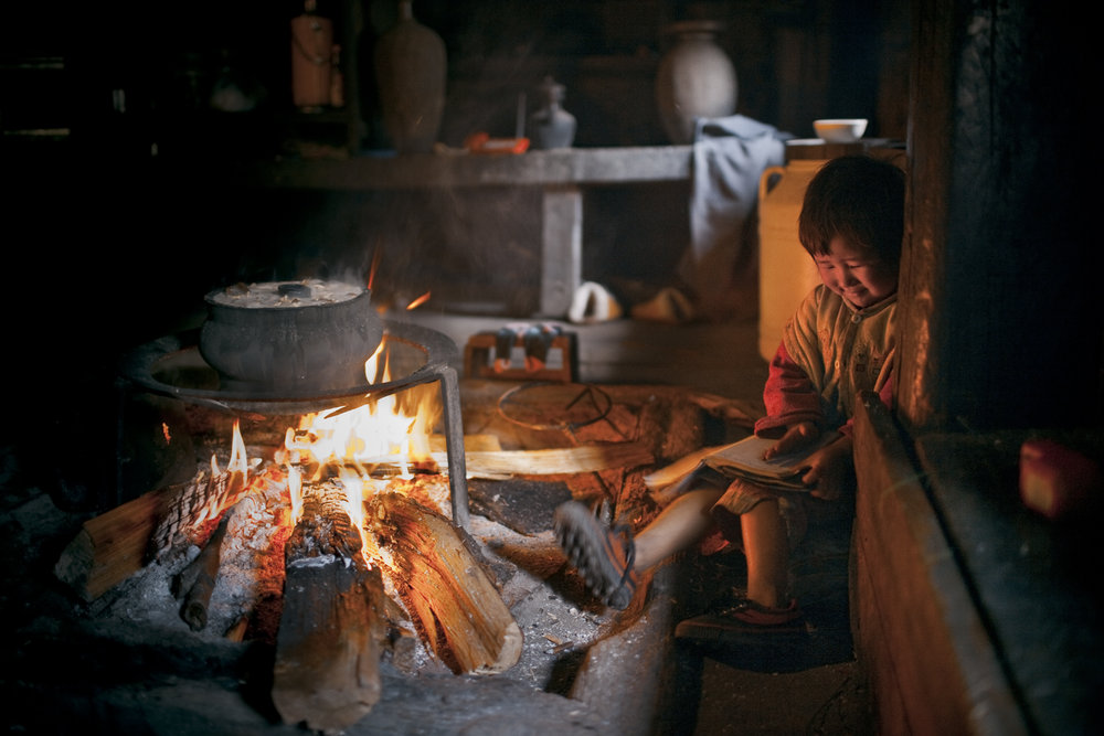 Qiunatong, Yunnan. A child reads near what will be New Year's Eve dinner. The village is primarily agricultural.