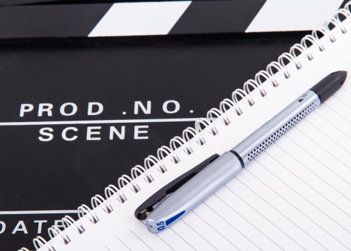 Black and white cinema clapper board with notebook and pen
