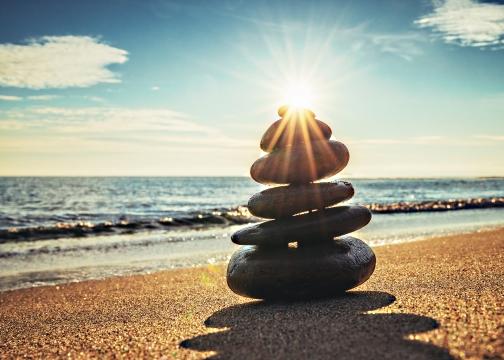 Sunrise shot of balanced stone stack on beach