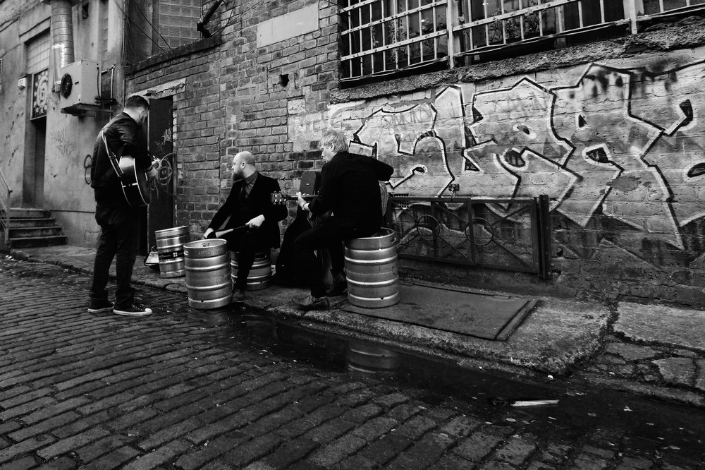 This is a candid shot of the band practicing in the alleyway behind Nice and Sleazy's before a gig.
