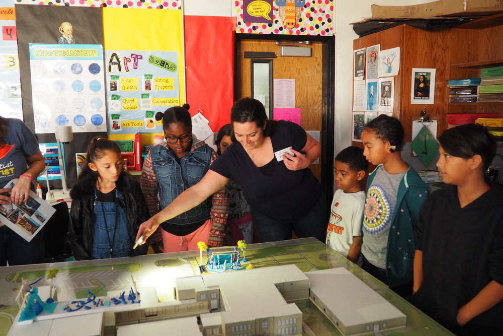Volunteer Architect, Lorrie Tumlinson, demonstrates to Blackshear students how the sun moves across the campus on a scaled model to emphasize the importance of shade.