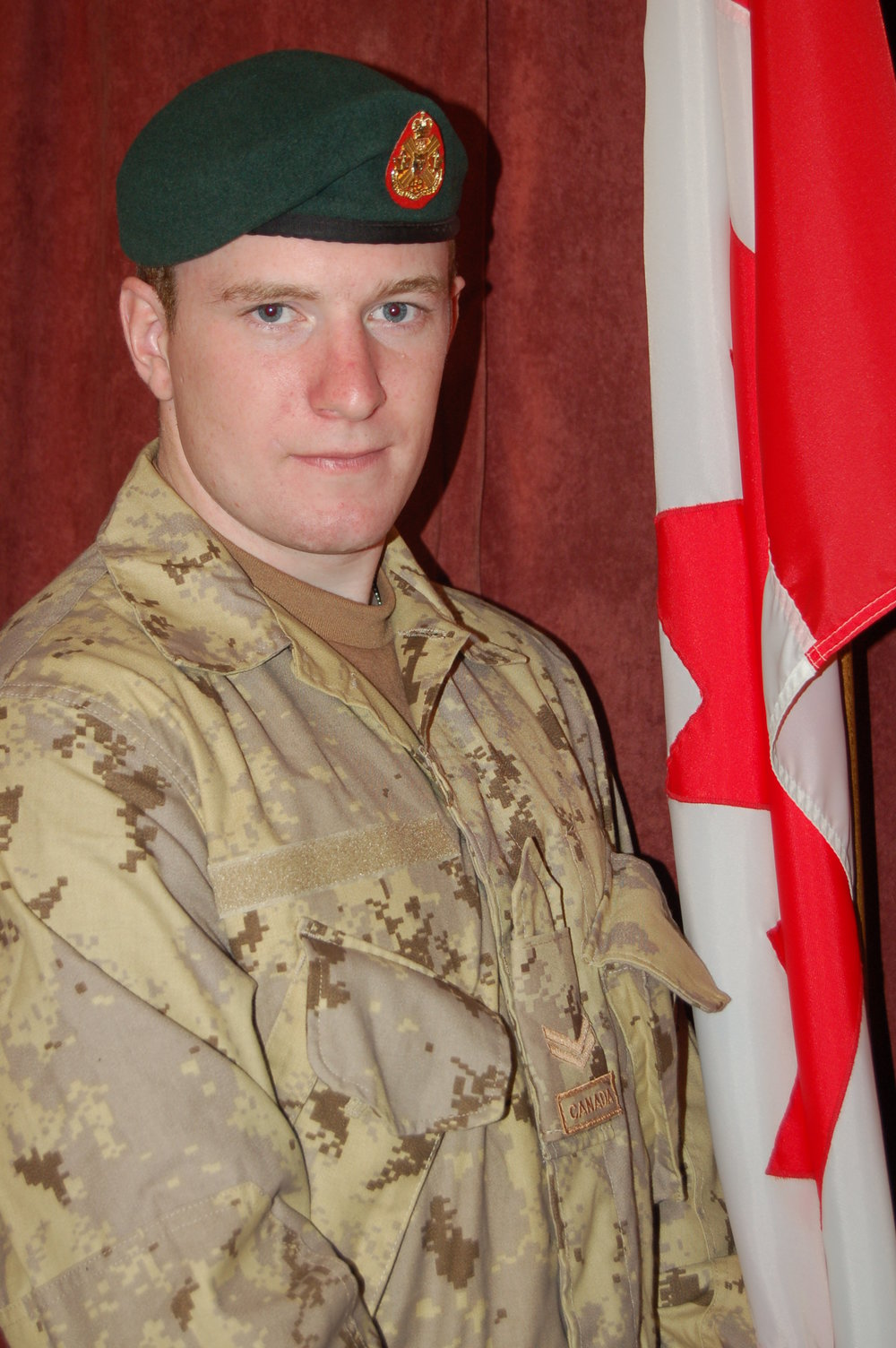 Chad Ford infantry reservist posing next to Canadian flag