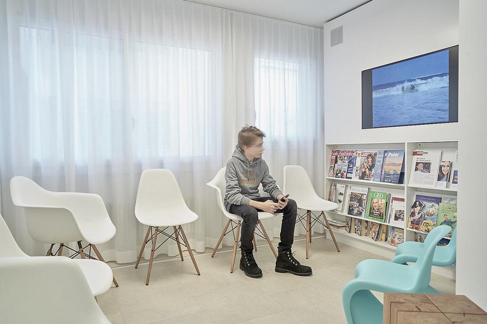 Das helle Wartezimmer der Praxis KIEFERORTHO EINSIEDELN bietet Unterhaltung für Kinder, Jugendliche und Erwachsene