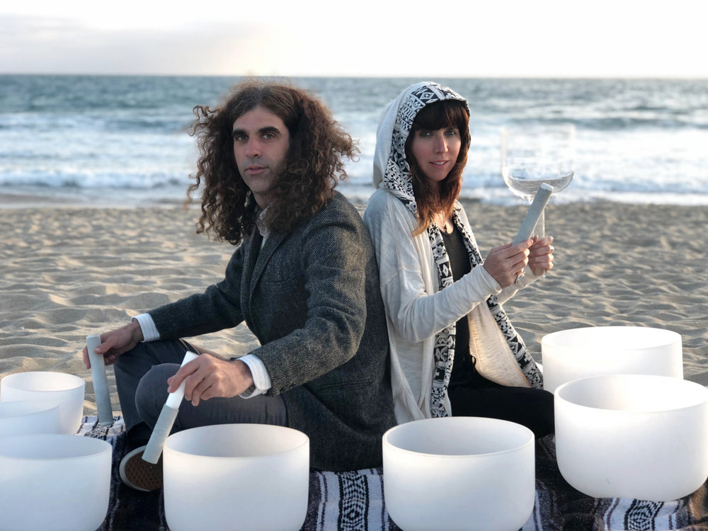 """We are musicians and sound healers currently based in Venice, California who originally met in New York City in 2001. Our journey has seen us exploring experimental jazz, rock & folk, electronic dance music, hip-hop and, most recently, music for meditation and sound baths. In 2012, we met a sound healer who gifted us our first singing bowl and started us on our way to merging our sound healing practice with our music. We embarked on a shamanic trip across the country, spending an extended time in the mountains of North Carolina and the deserts of Baja California, Mexico, and finally landing in Los Angeles. We began performing our music for yoga classes and our sound bath was born. We have been performing weekly on Friday evenings at Mystic Journey Crystals, as well as Sunset Sound Baths on Venice Beach, and other events throughout the city. The music on our new album """"Los Angeles Sound Bath"""" comes from these experiences. Peace, love, joy, and compassion to you, and thanks for listening! LOVE, Jenny & Seth, DYNASTY ELECTRIK"""