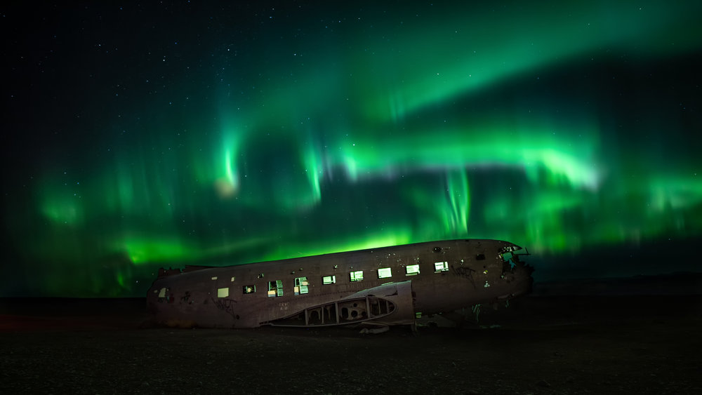 The Aurora Borealis above the old plane wreck near Vik. A very popular spot.