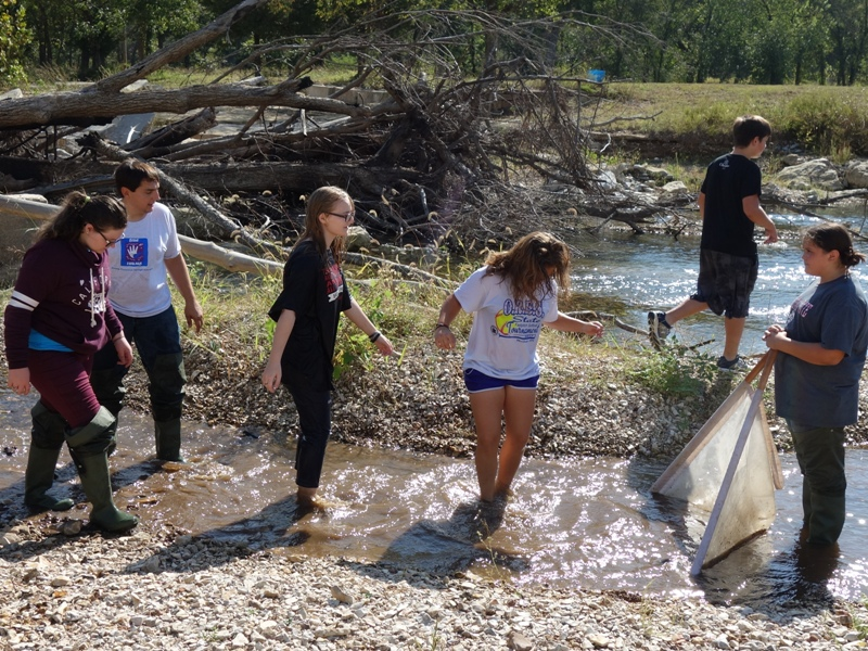 Rob Barossi of Blue Thumb (white T-shirt, left) helps Peggs 7th and 8th grade science students kick up invertebrates to see what they might find. The presence or lack of certain species tells us about a stream's health.