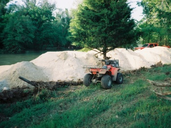 A four-wheeler is seen next to piles of dry fly ash that was being used illegally for road repair next to Spring Creek.