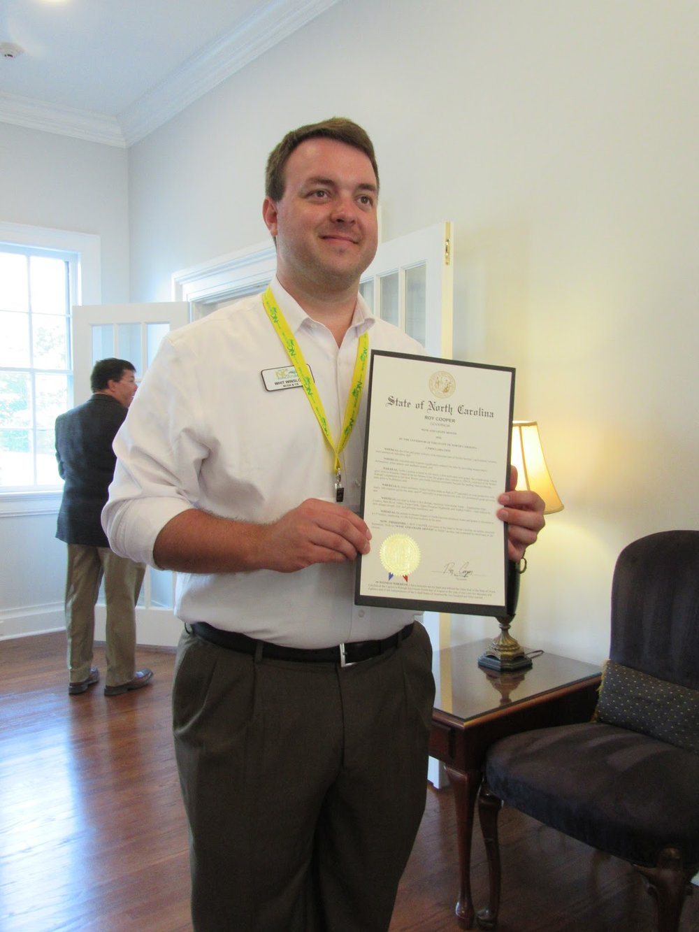 - Whit Winslow, Executive Director, NC Wine and Grape Council displays the official proclamation from Gov. Roy Cooper declaring September as NC Wine Month