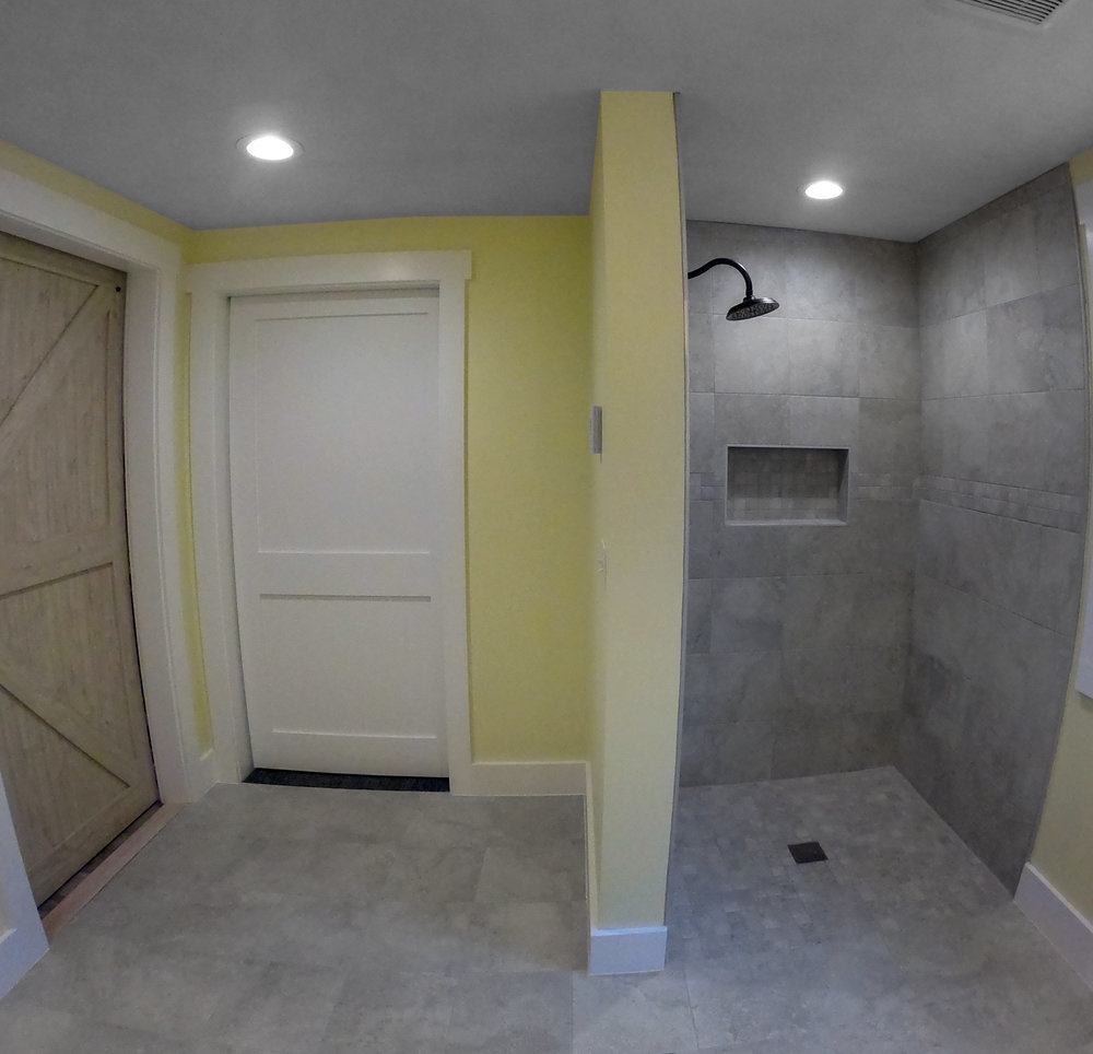 Handicap accessible bathroom with curbless shower & pocket doors.