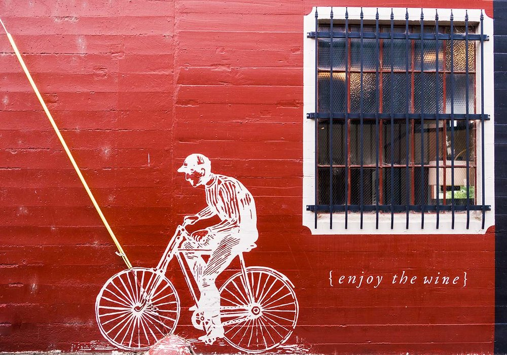 "On the side of t.h.e Interior is a bicyclist encouraging you to ""enjoy the wine."""