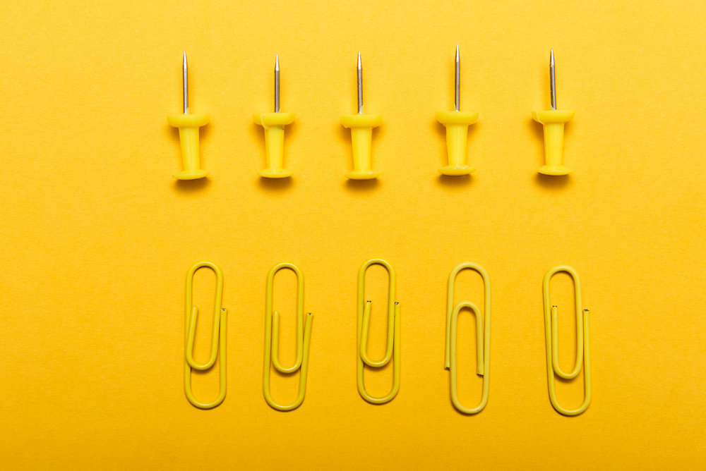 yellow-thumbtacks-and-clips-over-a-yellow-PY5SZZ7.jpg