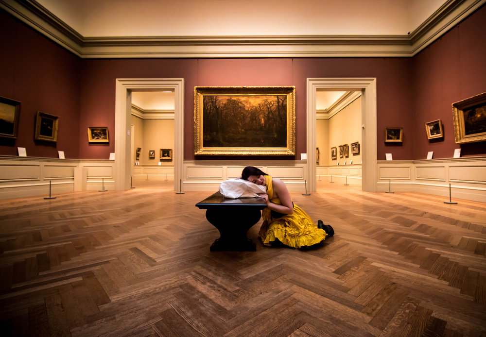 """There is something very surreal about this image that raises lots of questions. Who is the girl? What is she doing there? Why does she have a pillow? This inquisitive nature creates an interest and pulls you in to explore. The dress choice is interesting and mirrors the fancy gold photo frames in the background."" - Digital Camera Photographer of The Year 2019 Judging Panel"
