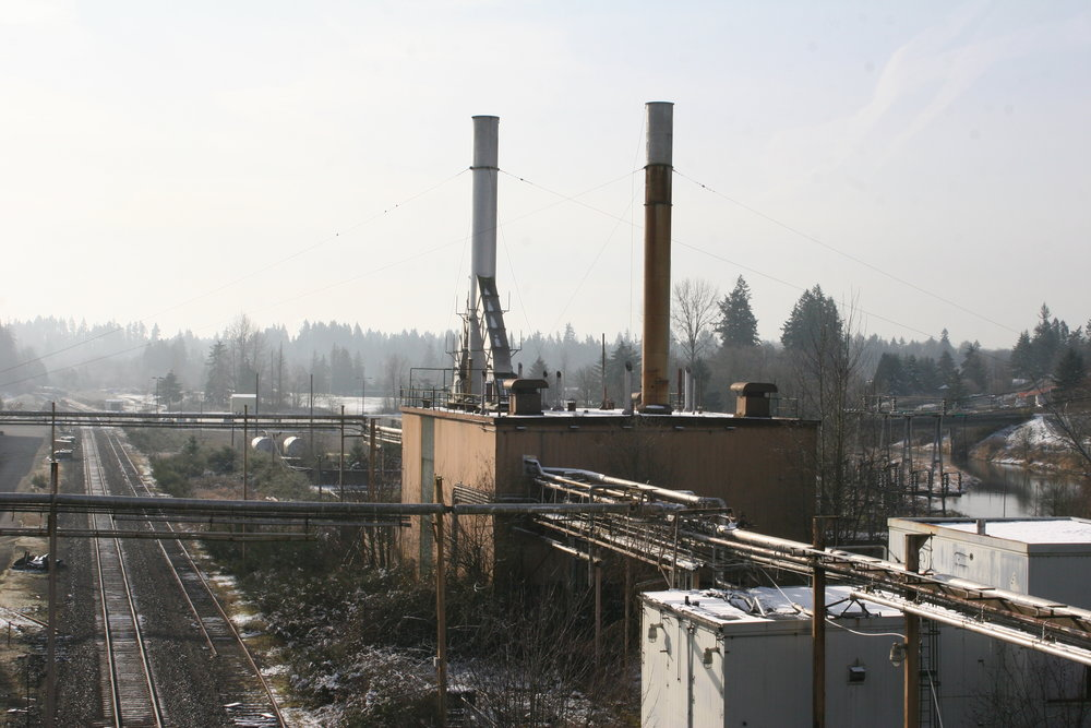 The old Olympia Brewing Company steam plant viewed from Capitol Boulevard's Carlyon bridge. This is where the old whistle blew for decades. Tumwater Valley Municipal Golf Course, where the whistle lives today, is in the distance.