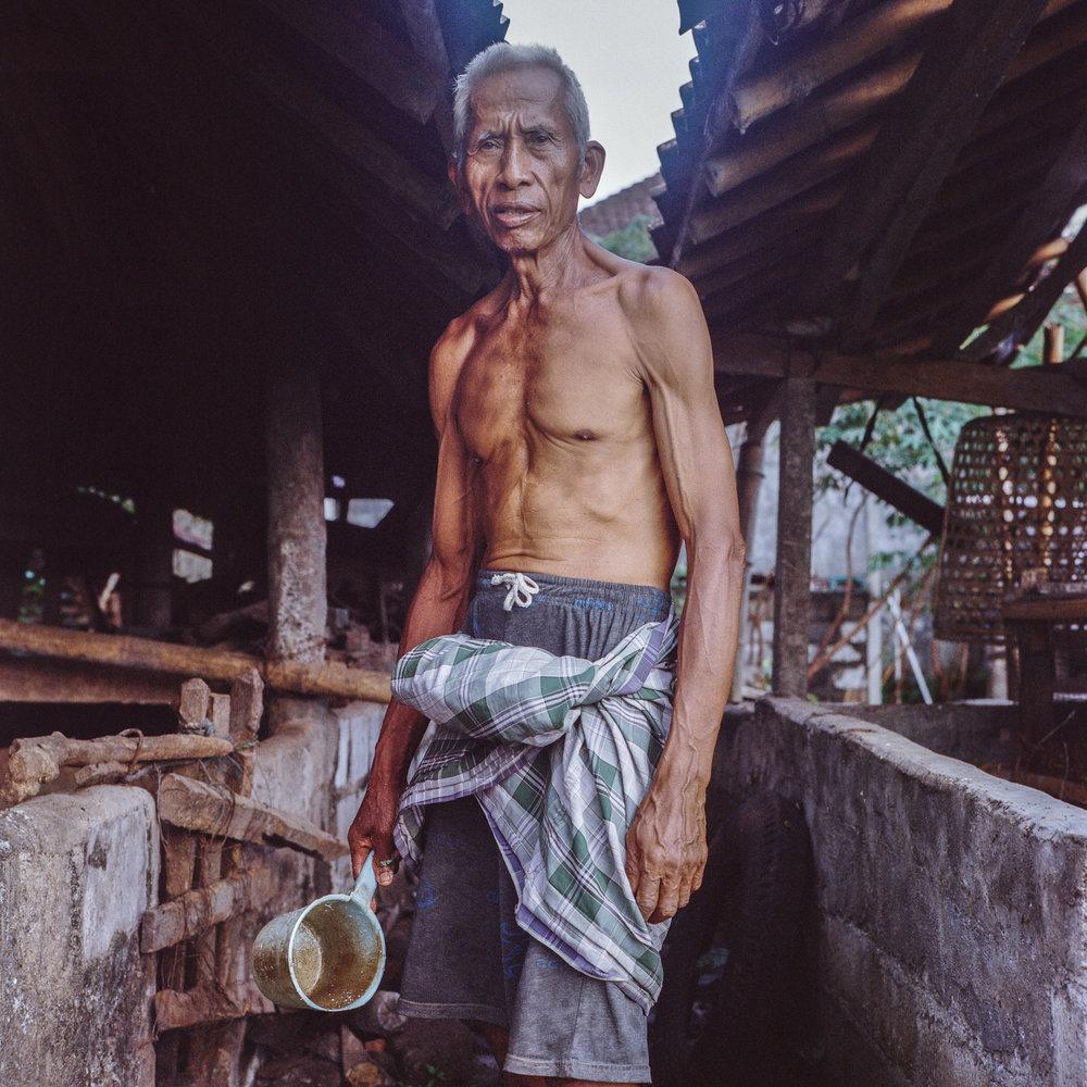 Pekak Tarti poses a portrait in his pig barn at Tunjuk Village, Bali, Indonesia.