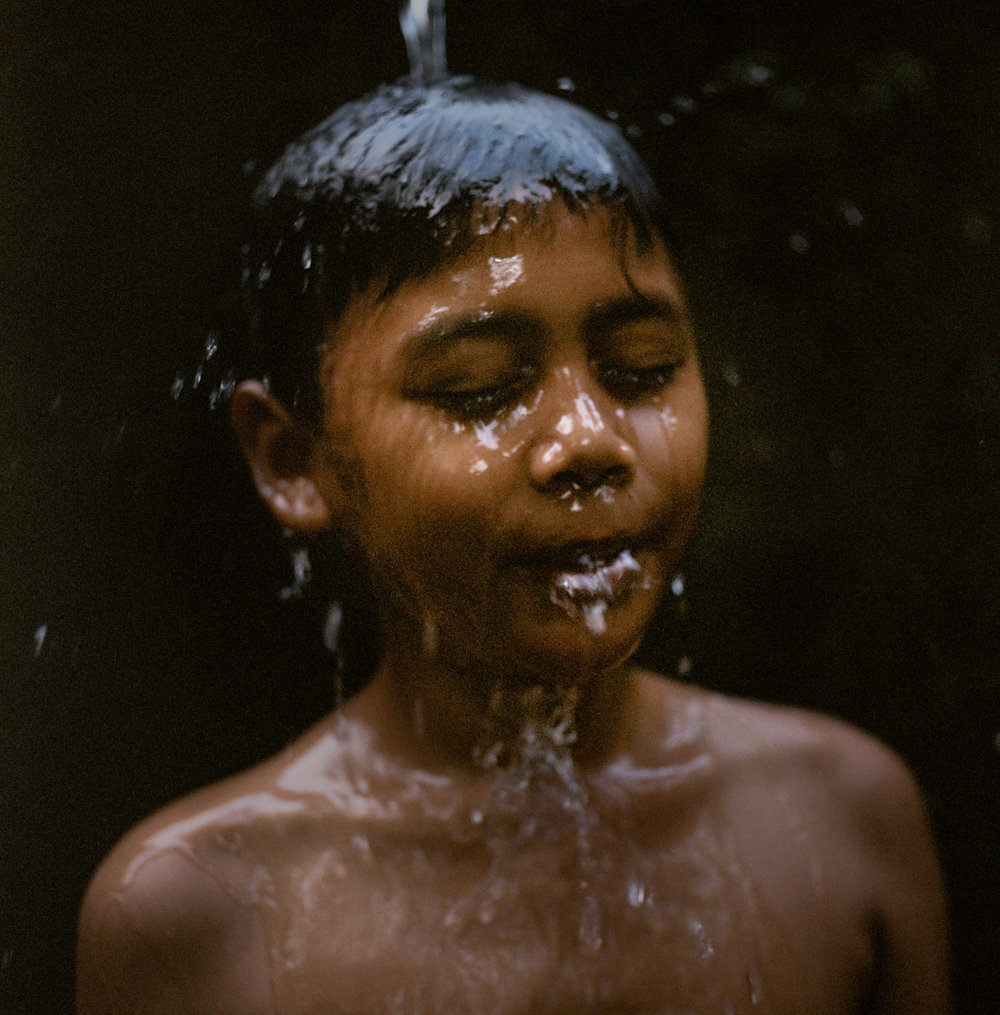 Kadek Abi takes bath a communal bathhouse at Tunjuk Village, Bali, Indonesia