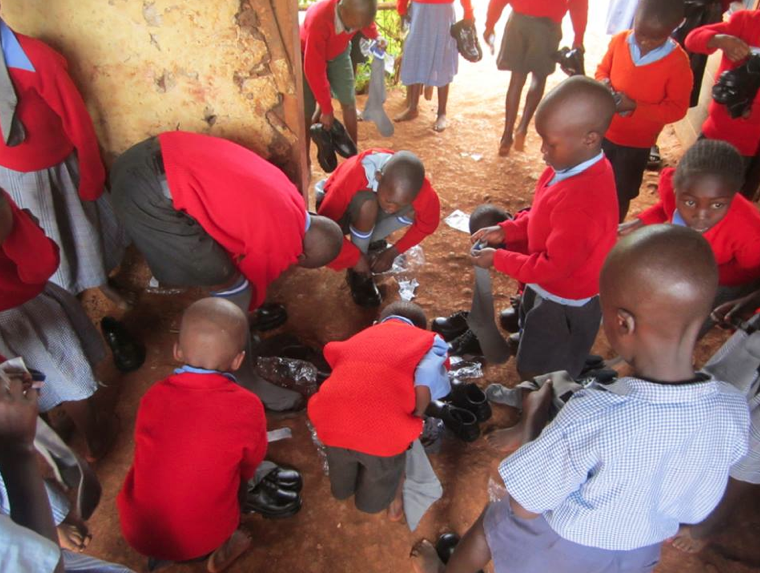 A few of the children at school putting on their new shoes.