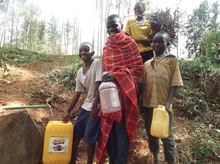 A clean water tank and tap installed by Arrive services the entire village of Nyaturubo.