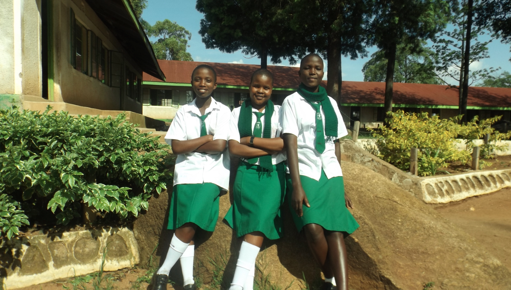 "Three of the ""Five Stars"" in front of their school courtyard and classrooms. From left to right: Delphine, Diana N, and Sylvia."