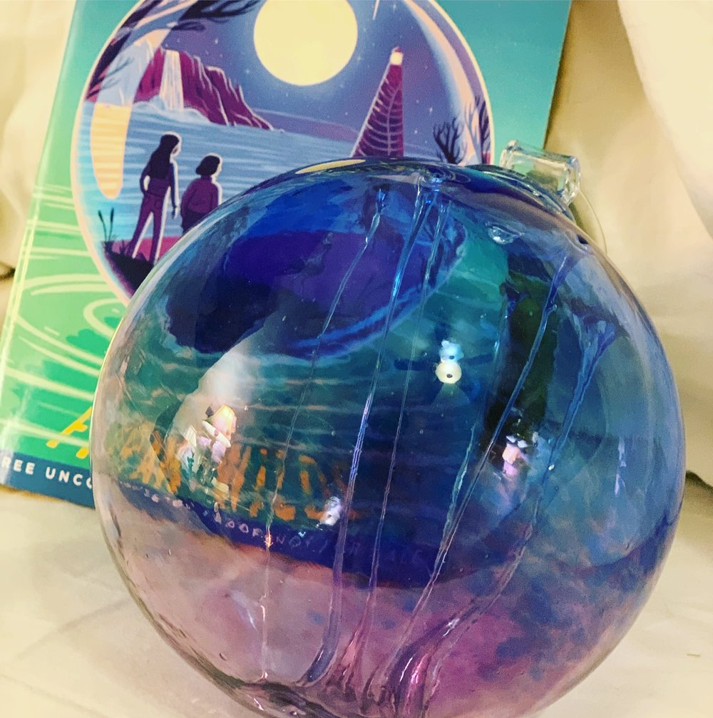 A blue glass witch ball, resting on an arc of my new book,  Riverland