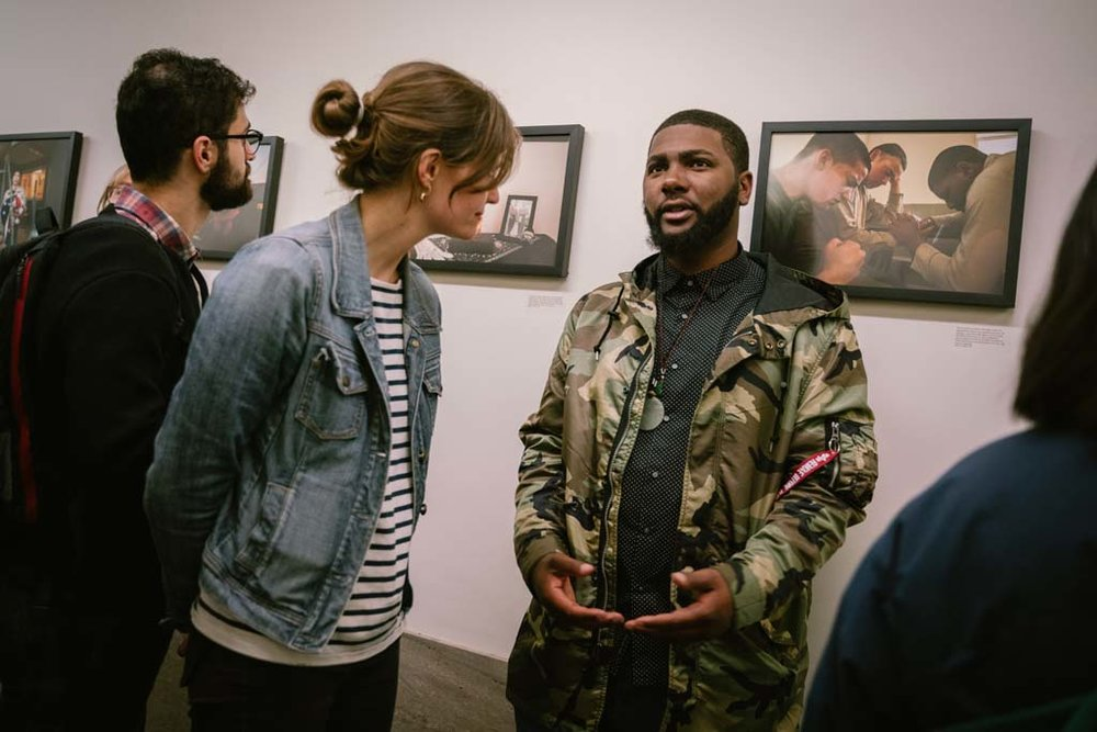 Workshop student Eugene Riley talks about his photographs on view at the Hall of Justice with exhibition visitors.