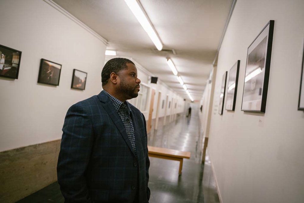 Workshop student Christopher Shurn looks at his photograph hung on the wall in the Hall of Justice for the first time.