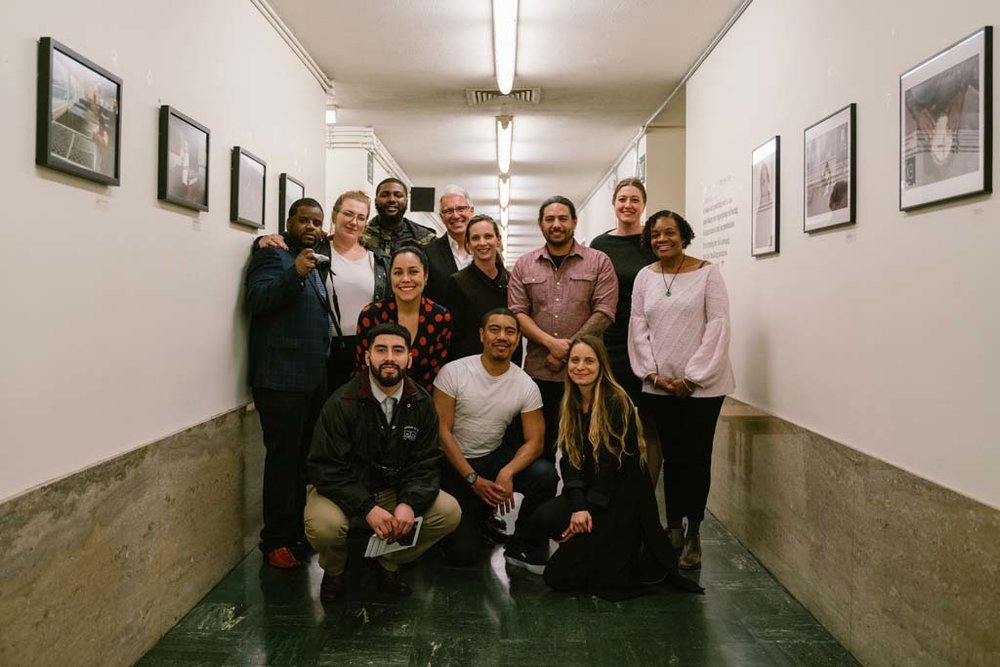 """Group photo of workshop students, CatchLight staff, photographer Brian L. Frank, Susan Brown and District Attorney George Gascón in the hallway that is home to """"Visions of Justice"""" on view through April 1, 2019."""