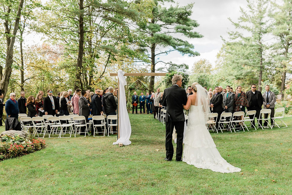 Father and daughter walking down the aisle green orchard wedding bride