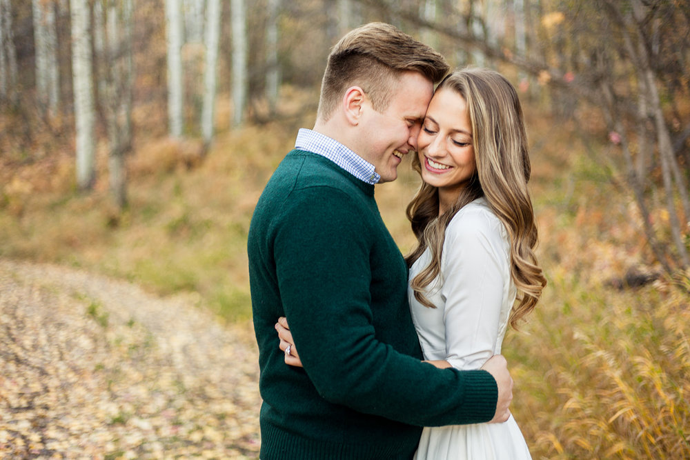 Eliza and Josh chose to have their engagement pictures done in the beautiful fall leaves! Josh chose a dark green sweater that perfectly contrasted the foliage, and Eliza wore an off-white dress that contrasted Josh. Notice Josh's subtle pattern with his button-up shirt underneath his sweater!