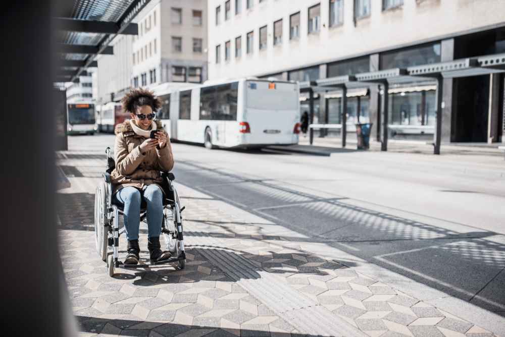 Disabled-woman-in-wheelchair-using-smart-phone-and-waiting-for-a-bus-955624950_5962x3980.jpeg