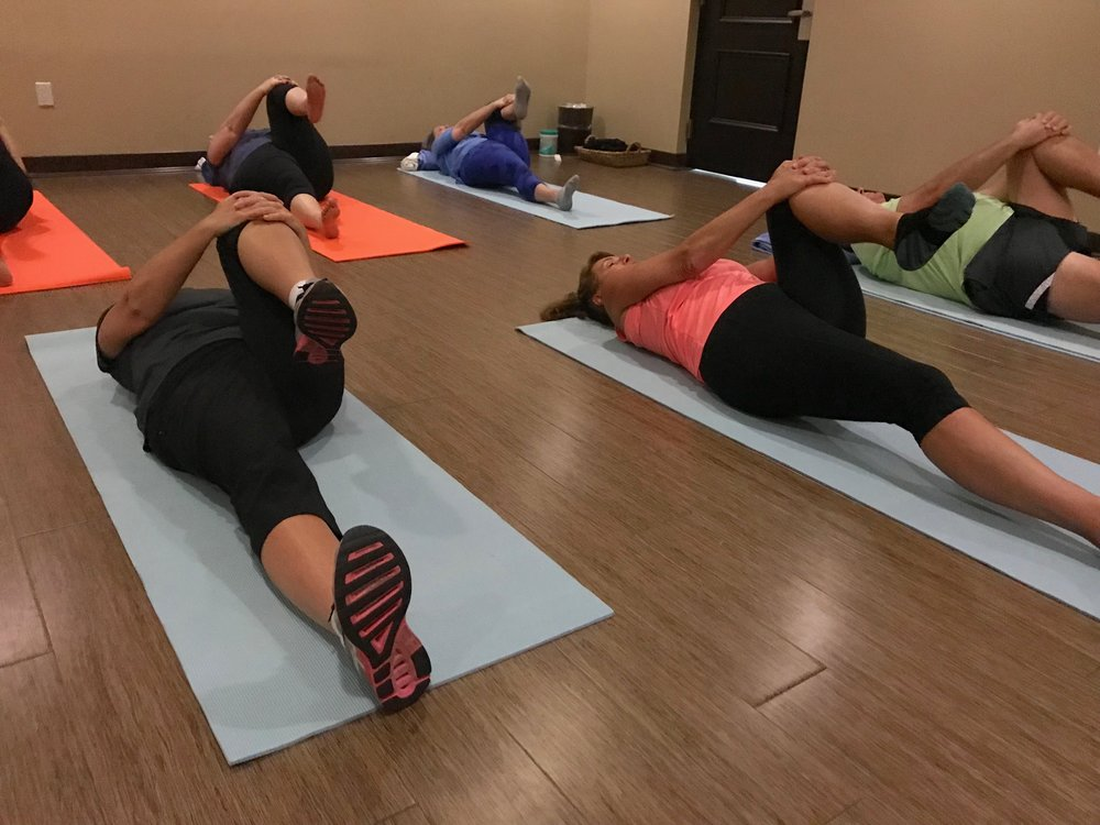 Boot camp clients relax during stretch class  in the studio.